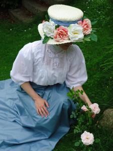 Rosenhatt i rosenträdgård. Dräkten hör hemma runt år 1903.